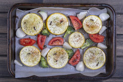 Die Zucchini, Tomaten, Brokkoli und Zwiebel, gewässert mit Olivenöl bereiteten sich auf Backbleche für das Backen im Ofen vor Bes Stockfotografie
