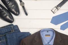 Die zufällige Kleidung und das Zubehör der Männer auf hölzernem Hintergrund Lizenzfreie Stockfotos