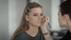 Die zukünftige Braut kam zu einem Schönheitssalon zum Make-upkünstler auf dem Make-uptest Mädchen, das im netten Lächeln des Raum stock video footage