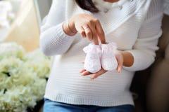Die zukünftige Mutter hält die Beuten in ihren Händen Sie ist sehr MU stockfoto
