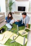 Die zusammenbauenden Möbel der jungen Familie am neuen Haus stockfotografie