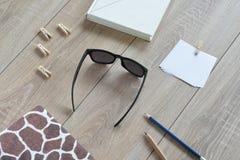 Die Zusammensetzung des Weiß und beschmutzten der Bücher, der Aufkleber, der Bleistifte, der Klammern und der Sonnenbrille Stockbild