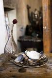 Die Zusammensetzung eines Vase, rosafarben und der Platte füllte mit Muscheln Stockfotos