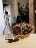 Die Zusammensetzung eines Vase, verwelkt stieg, des Mais, des Granatapfels und des Korbes, der mit verwelkten Blumen gefüllt wurd Lizenzfreies Stockfoto