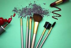 Die Zusammensetzung von einem Satz Make-up auf einem Türkishintergrund mit Schatten und Nagellack Stockfoto