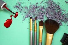 Die Zusammensetzung von einem Satz Make-up auf einem Türkishintergrund mit Schatten und Nagellack Lizenzfreies Stockfoto
