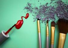 Die Zusammensetzung von einem Satz Make-up auf einem Türkishintergrund mit Schatten und Nagellack Lizenzfreie Stockfotos