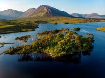 Die zwölf Kiefern-Insel, stehend auf einem herrlichen Hintergrund, der durch die scharfen Spitzen eines Gebirgszugs gebildet wurd lizenzfreie stockfotografie