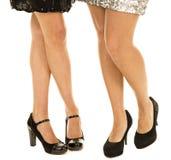 Die zwei Beine der Frauen, die schwarze Fersen gegenüberstellen Stockbild
