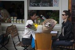 Die zwei Frauen kauften Blumen im Markt und saßen an einem Café im Freien und sprachen Stockfoto