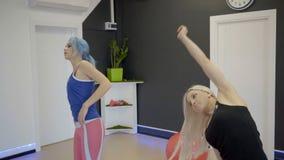 Die zwei Freundinnen, die herum ihre Hände während des exersice in der Luxusturnhalle drehen stock footage