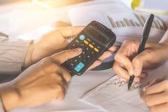 Die zwei Geschäftsfrauhand, die zusammen mit Finanzdaten arbeiten und das Geschäftsdiagramm berichten über Schreibtisch Stockfoto