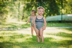 Die zwei kleinen Babys, die mit Gartenberieselungsanlage spielen stockfotos