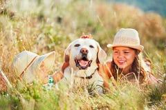 Die zwei Mädchen umarmen den Hund Lizenzfreie Stockbilder
