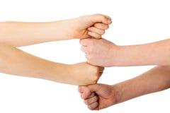 Die zwei vier Fäuste der Kinder, die auf einander, getrenntes Weiß liegen Lizenzfreies Stockbild