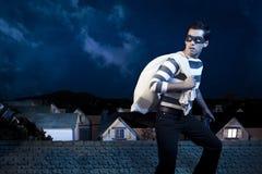 Dieb auf dem Dach eines Hauses nachts stockbild