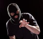 Dieb Burglar in der Maske, die eigenhändig ergreift Verbrechen-Mann im Schwarzen lizenzfreie stockfotografie
