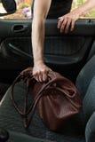 Dieb, der die Tasche der Frau vom Auto stiehlt Stockbild