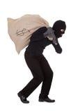 Dieb, der eine große Tasche des Geldes trägt Stockfoto