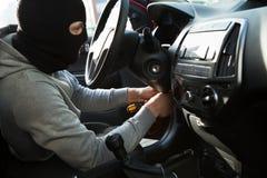 Dieb, der Schraubenzieher im Auto verwendet Stockbilder