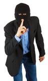 Dieb in der schwarzen Maske im Anzug mit dem Finger, der signalisiert, um durchaus zu sein Stockbilder