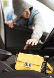 Dieb, der Tasche vom Auto stiehlt Lizenzfreie Stockfotos