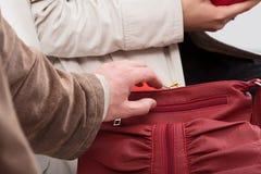 Dieb, der versucht, eine Geldbörse zu stehlen Stockfotos
