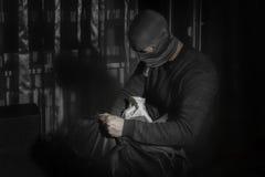 Dieb in einer Maske und mit einer Taschenlampe im Raum setzt die Beute in eine Tasche ein lizenzfreie stockbilder