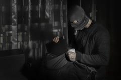 Dieb in einer Maske und mit einer Taschenlampe im Raum setzt die Beute in Tasche ein stockfotografie