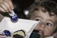 Diebstahl einer Schokolade. Lizenzfreies Stockfoto