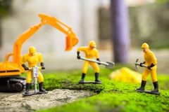 Diecast Construction Toys. Excavator Toys and Three Construction Worker with Shovel and Demolition Hammers Toys Royalty Free Stock Photos