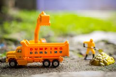 Diecast Construction Toys. Excavator Toys and Construction Worker with Shovel Digging Soil Stock Images