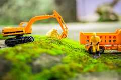 Diecast Construction Toys. Truck Toys and Construction Worker, and Excavator Toys Lifting Stone Stock Photography