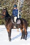 Dieci anni di ragazza che monta un cavallo nell'inverno Immagini Stock Libere da Diritti