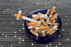 Died cigarette. A cigarette died in an ashtray on a white background Royalty Free Stock Images