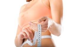 Dieet - de jonge vrouw meet haar taille Stock Afbeeldingen