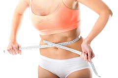 Dieet - de jonge vrouw meet haar taille Stock Afbeelding