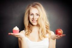 Dieet Gezonde Vrouwenholding Apple en Cake Stock Afbeeldingen