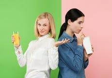 Dieet Het op dieet zijn concept Gezond voedsel Mooie Jonge Vrouwen die tussen sprankelend fruitjus d'orange en unhelathy kiezen royalty-vrije stock afbeeldingen