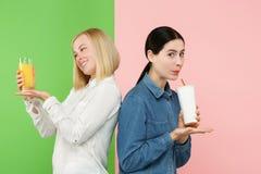 Dieet Het op dieet zijn concept Gezond voedsel Mooie Jonge Vrouwen die tussen sprankelend fruitjus d'orange en unhelathy kiezen royalty-vrije stock foto's