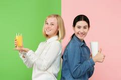 Dieet Het op dieet zijn concept Gezond voedsel Mooie Jonge Vrouwen die tussen sprankelend fruitjus d'orange en unhelathy kiezen stock foto