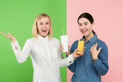 Dieet Het op dieet zijn concept Gezond voedsel Mooie Jonge Vrouwen die tussen sprankelend fruitjus d'orange en unhelathy kiezen stock foto's