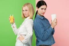 Dieet Het op dieet zijn concept Gezond voedsel Mooie Jonge Vrouwen die tussen sprankelend fruitjus d'orange en unhelathy kiezen royalty-vrije stock fotografie