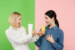 Dieet Het op dieet zijn concept Gezond voedsel Mooie Jonge Vrouwen die tussen sprankelend fruitjus d'orange en unhelathy kiezen stock fotografie