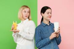 Dieet Het op dieet zijn concept Gezond voedsel Mooie Jonge Vrouwen die tussen sprankelend fruitjus d'orange en unhelathy kiezen stock afbeelding