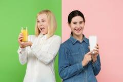 Dieet Het op dieet zijn concept Gezond voedsel Mooie Jonge Vrouwen die tussen sprankelend fruitjus d'orange en unhelathy kiezen royalty-vrije stock foto