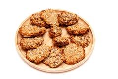 Dieet magere koekjes van het close-up de eigengemaakte natuurlijke havermeel met zaden op een ronde houten die plaat op een witte stock foto
