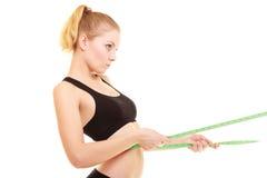 Dieet slank blondemeisje met maatregelenband die taille meten Royalty-vrije Stock Foto's