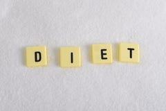 Dieetblokletters in kruiswoordraadsel over suikerstapel op zoete korrelige witte suikertextuur worden geïsoleerd in het op dieet  Stock Afbeeldingen