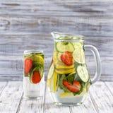 Dieetdetoxdrank met citroensap, rode aardbei, komkommer en muntbladeren in duidelijk water met ijs Royalty-vrije Stock Foto's